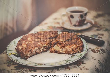 Delicious yummy apple pie on a plate and a cup of tea in the background done in retro style