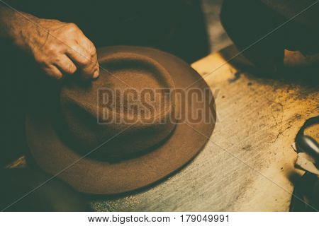 Close up shot of a hatter's hands manufacturing a hat.