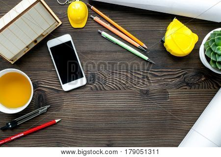 Architects workplace with constructor tools with cup of tea and mobile on wooden table background top view mock-up