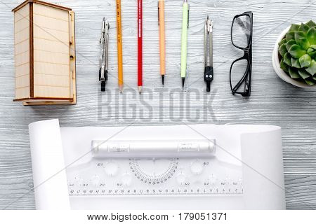 profession concept with architect desk and constructor tools and glasses on light wooden background top view
