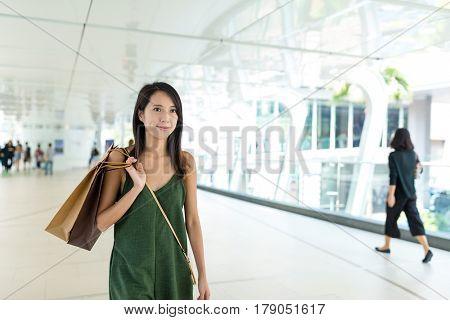 Woman holding shopping bag ans walking along the street