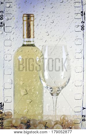 White wine bottle in strip film frame with glass and bunch of grapes behind wet glass