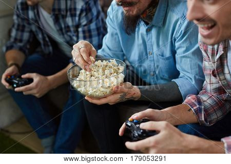 Closeup portrait of three excited adult men  enjoying video game battle and cheering, holding wireless controllers while sitting on couch in living room with popcorn