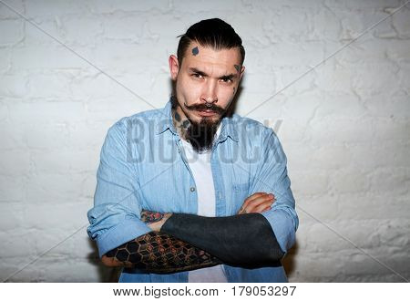 Saturated flash portrait of modern creative man: with beard, moustache and tattoos, looking  sullenly from under eyebrows at camera with hands crossed against white brick wall