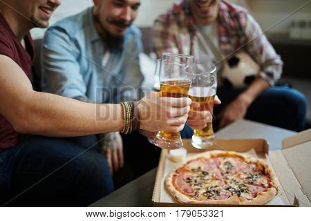 Closeup portrait of group of friends meeting at home toasting with beer and eating pizza while watching football match