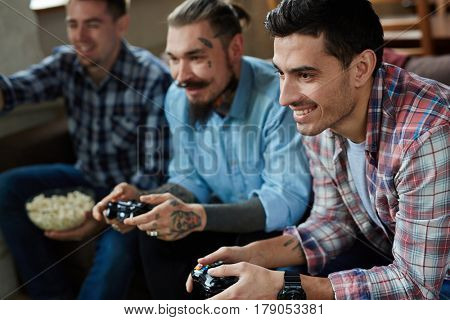 Portrait of three excited adult men enjoying video game competition and smiling cheerfully holding wireless controllers while sitting on couch in living room with popcorn