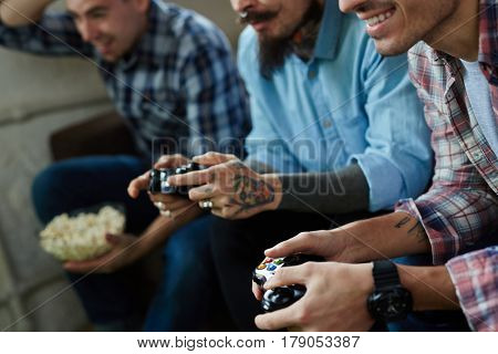 Young men with tattoos enjoying video game competition and smiling cheerfully holding wireless controllers while sitting on couch in living room with popcorn