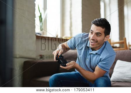 Portrait of handsome emotional adult man playing video game holding wireless controller and  smiling joyfully while sitting on couch at home