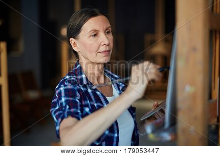 Mature student or teacher of art-school painting in workroom