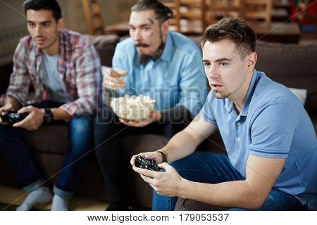 Group of three modern adult men holding wireless controllers enjoying video game competition and having popcorn