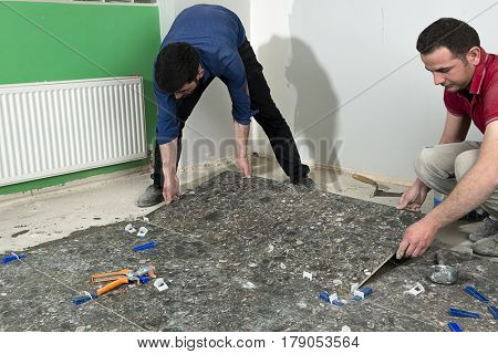 Real construction workers installing ceramic tiles.