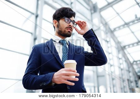 Posh young man in suit and eyeglasses holding drink