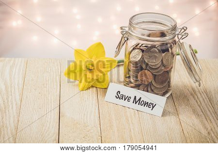 Save Money money jar savings motivational concept on wooden board with yellow daffodil flower