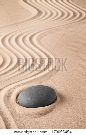 Zen background with stone and pattern of lines in the sand. Focus on concentration and spirituality for harmony and purity. Spa wellness therapy or yoga theme.