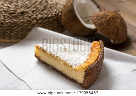 Coconut Tart Pie Slice on White Paper and Wooden Table Background