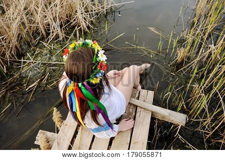 beautiful young girl in a white chemise and a wreath of flowers on her head sitting on a wooden bridge on a background of the river. The Celebration Of Midsummer
