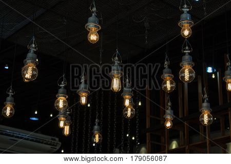 Lighting on the chandelier in the lamplight light bulbs hanging from the ceiling lamps on the dark background .Coffee Shop Decoration . modern, old, orb, power plant, reflection, restaurant, retro, room, party, shiny, technology, transparent, vintage.
