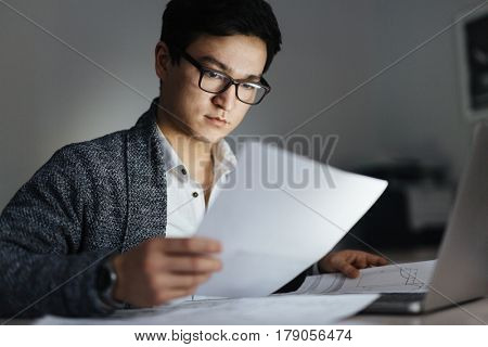 Portrait of busy Asian man wearing glasses and casual wear sorting documentation and working with laptop in dark room late at night, his face lit up by screen