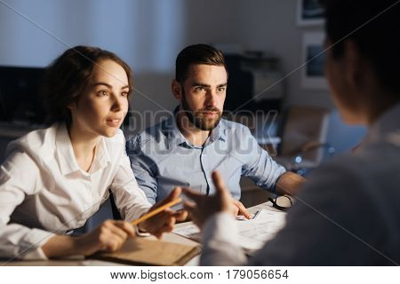 Portrait of three colleagues working overtime in dark office late at night: brainstorming at meeting table while collaborating on project trying to finish by deadline