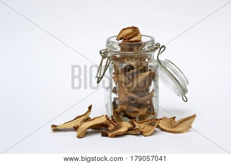 Glass jar full of mushrooms, chopped and dried penny buns, with some slices spilled around