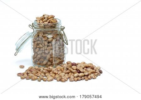 Glass jar full of brown beans, with some beans spilled around