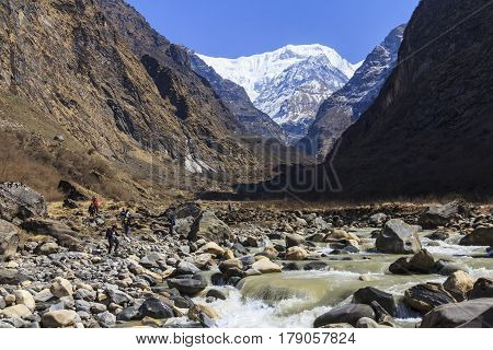 ANNAPURNA NEPAL - APRIL 13 2016 : Tourists and river in Himalaya mountain valley trekking trail to Annapurna basecamp Nepal