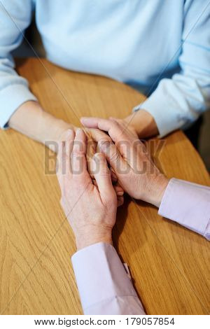 Senior man holding hands of his spouse