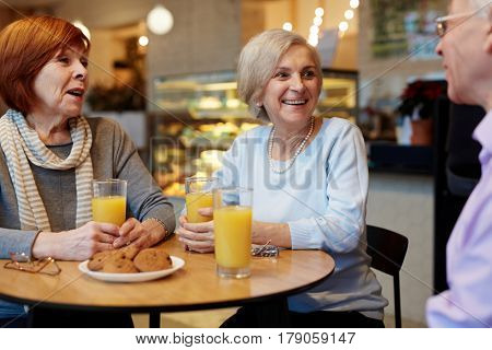 Old buddies sitting by table in cafe and having talk