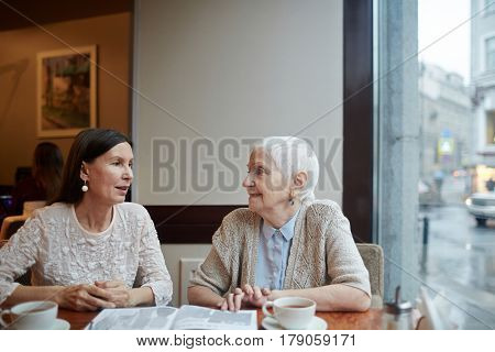 Two female buddies discussing article from magazine in cafe