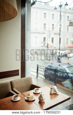 Two cups of tea, sugar-bowl, brewing-teapot and sandwiches on wooden table in empty cafe