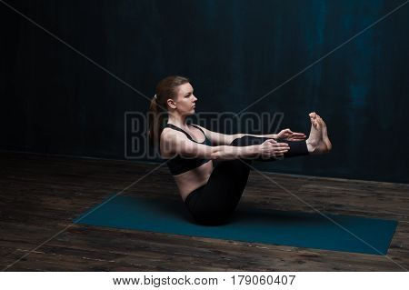 Sporty young woman exercising on blue mat indoors. Fit girl wearing black sportswear practicing yoga asana against dark wall. Fitness and healthy lifestyle concept.