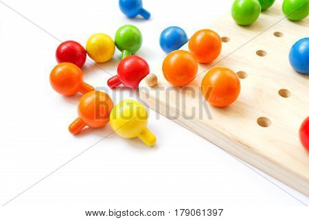 Colored pegs board, wood beads on white background. Shallow DOF