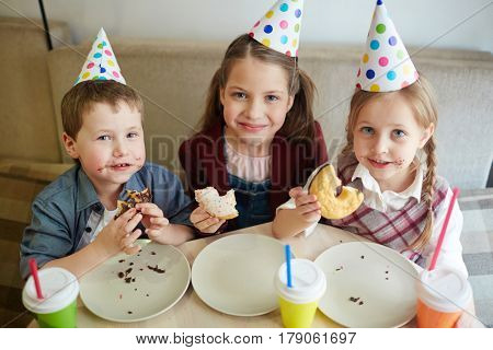 Hungry buddies eating tasty glazed donuts at birthday party