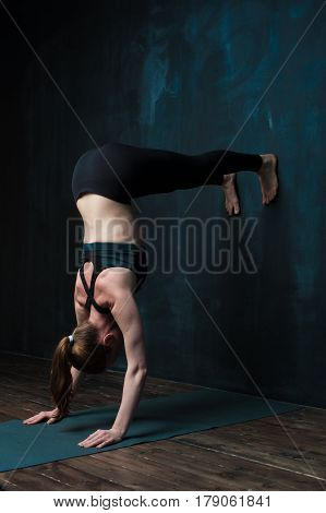 Sporty young woman practicing advanced yoga pose. Fit girl doing hand stand exercises near dark blue wall. Fitness and healthy lifestyle concept.