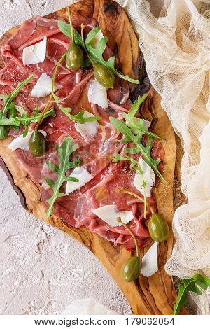 Beef carpaccio on olive wood serving board with capers, olive oil cheese and arugula, served with gauze textile over beige concrete texture background. Top view with space for text.