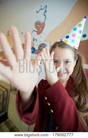 Little girl in birthday-cap making teasing gesture