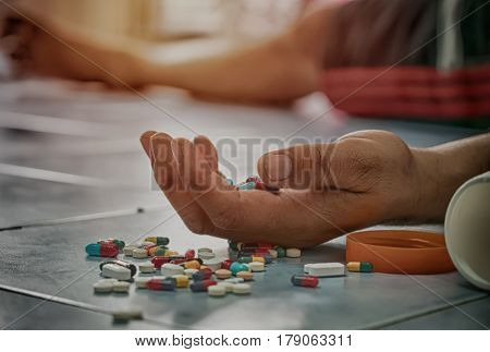 Overdose - close up of pills and addict lying on the floor