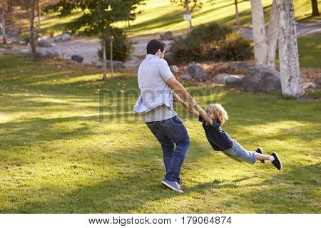 Father Swinging Son By His Arms In Park