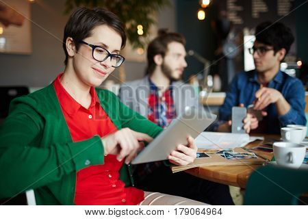 Young woman with touchpad browsing in the net with colleagues talking on background