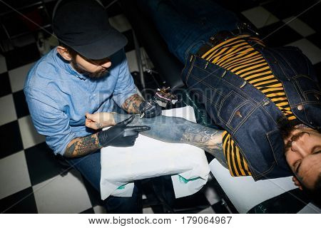 Owner of tattoo salon serving client