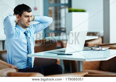 Tired handsome financial manager putting hands on nape and searching mistake in his calculations on laptop, waist-up portrait
