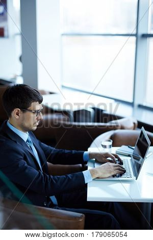 Portrait of young bearded financial manager sitting in office lobby and preparing annual accounting reports, profile view