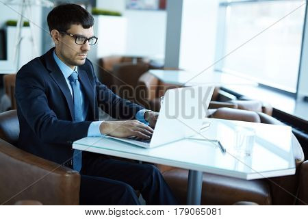 Handsome bearded employee wearing classical suit sitting in cozy small cafe and working on modern laptop, notebook, pen and glass of water located on table