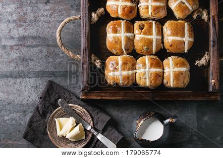 Hot cross buns in wooden tray served with butter, knife and jug of cream on textile napkin over old texture metal background. Top view, space. Easter baking.