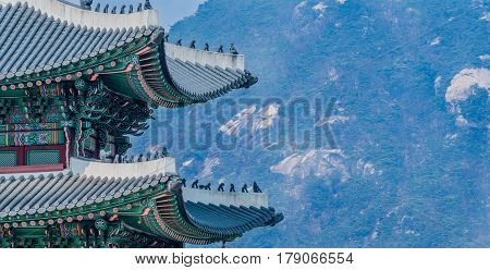 Seoul South Korea March 18 2017:Tiled roof of Seoul's Gyeong Bok Gung Palace in stunning colors with small figurines on the eves set against a background of a mountain side with visible boulders.