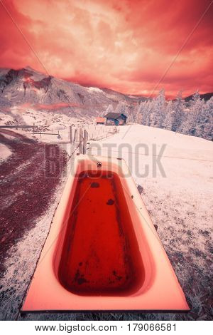 an infrared shot of a bathtub filled with rainwater, the simmental valley in the background. photo taken with a modified canon 40d.