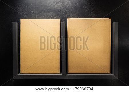 cardboard box on wooden shelf at black background surface