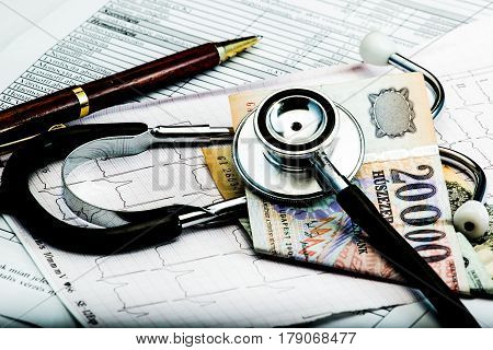 Stethoscope and money symbol for health care costs or medical insurance on electrocardiogram.