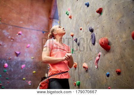 fitness, extreme sport, bouldering, people and healthy lifestyle concept - young woman with chalk bag exercising at indoor climbing gym wall