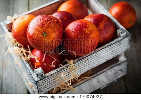 Fresh ripe Sicilian oranges in a wooden box on an old background. Selective focus.